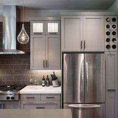 Every inch of space is put to use in this streamlined kitchen, including a slim strip of cabinetry that serves as wine storage. Custom-designed, locally built cabinets in a soft gray hue are clean and crisp against white Caesarstone countertops and bright white trim.