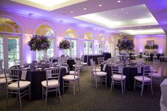 Purple Wedding Reception Table Decor   Silver Chiavari Chairs, Purple and Ivory Tall Table Floral Centerpieces, and Purple Uplighting   Tampa Wedding Venue Tampa Palms Golf and Country Club