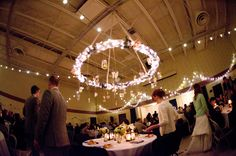 DIY Wedding: The reception was held in the gym of our church. We decorated using string lights (stocked up during Christmas season!) and the church provided us with this brass ring that we covered with lights and hung from the middle of the ceiling to show where the head table was. #blatchleywedding