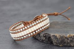 This is hand woven bracelet made with light brown color waxed polyester cord weaved together with faceted silver plated beads and tube shape turquoise