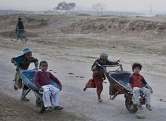 Pakistani boys compete in a wheelbarrow race at a slum on the outskirts of Islamabad, Jan. 3, 2012. (Anjum Naveed/Associated Press)