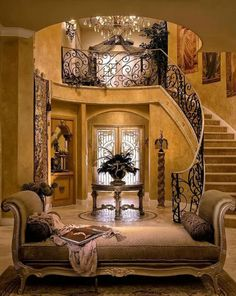 Mediterranean Home with sweeping staircase, iron railing. Draperies in this style DesignNashville.com