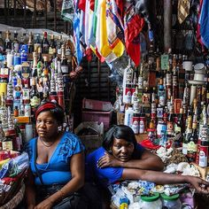 In a street market in Cap-Haitien Haiti's second largest city located on its northern coast Maryse right and her friend Martine sell religious products used for Vodou rituals and ceremonies. Photo by @fotokonbit student Philomene Joseph 20. FotoKonbit.org students shot all the photographs for the NGM story HAITI ON ITS OWN TERMS in the December issue of the magazine. Often Vodou is miscast and vilified as devil worship when in fact it is the worship of nature and spirits and God the Father…