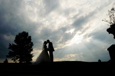 Katherine and Mark – Feature Wedding by Caprisio, LLC. Trump National Golf Club Bedminster NJ, Wedding. Bride and Groom silhouette with sun rays on the golf course. http://www.caprisio.com
