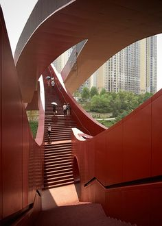 The bridge's sequence of walkways connect river banks, the road and a park, all located at different heights. First unveiled by the firm in 2013, the sinuous form was inspired by the never-ending surface of a Möbius strip.