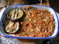 Moussaka - It has eggplant, onions, tomatoes and peppers. It can be spicy depending on how it is made.