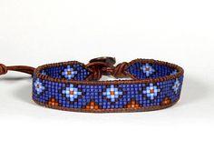 Cuero de grano azul medianoche Delica semilla wrap pulsera diamantes escalonados Esta pulsera está realizada con rocallas de Delica 11/0. El ancho es de una media pulgada. Un campo de granos de la semilla azul noche metálico, con patrón de diamantes azul y naranja, tejido entre dos cordones de cuero natural lred teñido marrón USA. Se cierra en unos 7.5, 8 1/2, 9 1/2 con el botón de cobre tejido patrón tribales. Hecho para el hombre o mujer. Pulseras de Aerieanna todos están...