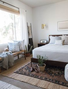 How to design a california casual master bedroom with vintage layers rugs and woven shades and eclectic decor accents.