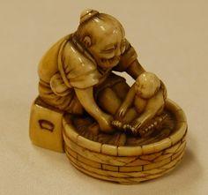 Old woman bathing baby. Japanese netsuke, made of ivory, 19thC