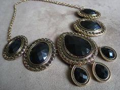 Colar confeccionado em metal na cor ouro velho com aplicação de chatons de acrílico preto.  Altura regulável R$82,90
