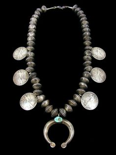This exquisite squash blossom necklace was made using a combination of Liberty dimes and half-dollar coins. Each bead is made with two domed Liberty dimes. The coin silver naja (center pendant) is set with a single natural turquoise stone. The dimes range from 1924 to 1945. The half dollars are from 1942 to 1945. The sterling silver cones are each stamped with three rain cloud symbols and the word sterling. The necklace has not been cleaned as many collectors prefer the Old Pawn look.