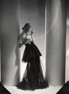Woman Wearing Mainbocher Dress ca. 1938 — Model wearing a gown with two-tiered black net skirt, white net bodice and shawl, satin belt with round clasp designed by Mainbocher; heavy gold bracelet and earrings by Mauboussin; hair upswept in pin curls. Vintage Mode, Vintage Gowns, Vintage Outfits, Vintage Style, Vintage Hats, Vintage Glamour, 1930s Fashion, Retro Fashion, Vintage Fashion