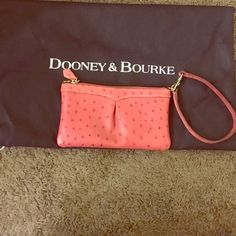 Authentic Dooney & Bourke Pink Ostrich Wristlet Absolutely adorable perfect condition pink leather ostrich wristlet. Red leather in the inside. Authentic Dooney. Comes with dust bag. Used a couple times. No scratches on leather. Stored in dust bag when not in use those couple times. Smoke free home and pet free.  Serial # J2190696 Dooney & Bourke Bags Clutches & Wristlets