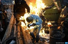 """UKRAINE, Kiev : Protesters catch fire as they stand behind burning barricades during clashes with police on February 20, 2014 in Kiev. Ukraine's embattled leader announced a """"truce"""" with the opposition as he prepared to get grilled by visiting EU diplomats over clashes that killed 26 and left the government facing diplomatic isolation."""