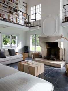 There's so many details about this loft- L-shaped couch, fireplace, library upstairs- loft living & lovely!