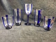 MIXED GROUPING OF COBALT BLUE STRIPE GLASSWARE INCLUDING ONE WINE GLASS, TWO ROCKS GLASSES AND TWO HIGHBALLS. ALL HANDMADE WITH BUN FEET (EXCEPT THE WINE GLASS).