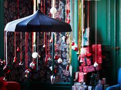Blauwe paraplu hangt van het plafond, versierd met rode linten en kerstballen in wit, rood en zilverkleur