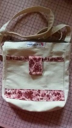Bolsinha tiracolo em algodão cru com detalhes em tricoline estampado e fechamento em zíper e frente em velcro.