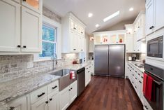 Brick backsplash. Making use of upper cabinet space with glass doors and lighting.