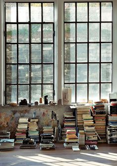 Book piles and industrial windows . Une grande baie vitrée au style industriel avec des piles de livres. verrière petits carreaux
