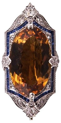 A brooch made for Daisy Buchanan: In the style of Art Deco, platinum over 14K gold, with a large central citrine, surrounded by sapphires and diamonds, American, circa 1920-1930. Clifford Baron Gallery.