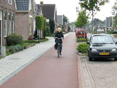An older woman rides her bike along a cycle path, past houses with driveways