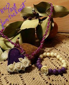Ciondolo a forma di cuore viola, piccole rose bianche su un lato e braccialetto abbinato. Toni sul viola e panna.