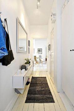 Lumineux ce couloir d'entrée adopte un miroir élargissant en apparence le passage. - White  corridor