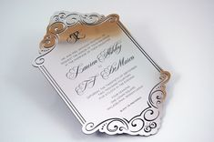 A custom chrome wedding invitation for a romantic wedding at the Four Seasons. Laser cut border and Swarovski crystal details.