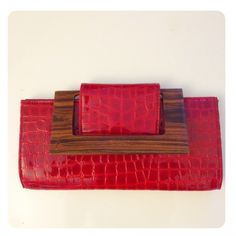 Ellie Clutch Patent Leather was $198 now $70.31.   A Classic rectangle clutch with a snapped flap closure. Add a hand-carved guyacan wood handle that can be used to carry or flipped down tho lie flat, and matte croc deerskin, and it becomes a totally exotic showpiece. Deerskin, Love Craft, Handbags On Sale, Hand Stitching, Patent Leather, Hand Carved, Exotic, Carving, Handle