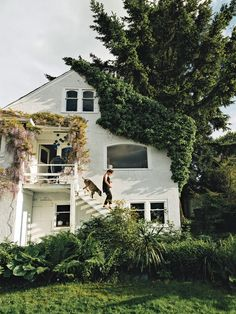 White stucco home exterior - Small second story porch - Lush green garden - Wisteria - 1942 cottage overlooking Vancouver's harbor
