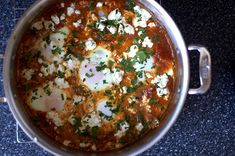 shakshuka, an Israeli dish of eggs poached in a spicy tomato sauce. served with warm pita bread or over rice