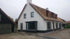 Mooi wit huis met rieten dak. Antraciete erker