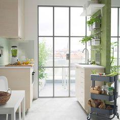 En moderne, lille og grønt køkken med HAGANÄS fronter af birketræsfiner.