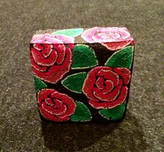 Roses painted on a brick by Linda Hallett.