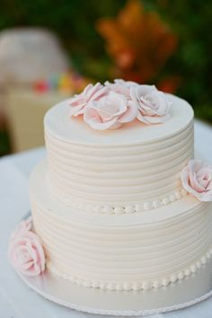 A white wedding cake with pink flowers | Kate Headley | Brides.com