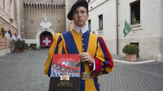 """FILE - In this Monday, Nov. 10, 2014 file photo, Swiss Guard David Geisser 24, poses with his book 'Buon Appetito', the Italian expression for """"enjoy your meal"""", at the Vatican. If an army travels on its stomach, what does the world's smallest army eat? Chef and Swiss Guard David Geisser sheds some light on the culinary tastes of the pope's army with a new cookbook """"Bon Apetit, Swiss Guard,"""" featuring recipes that feed the troops, and some menus inspired by the tastes of popes past and ..."""