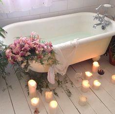 Candles, flowers, claw foot bath tub.
