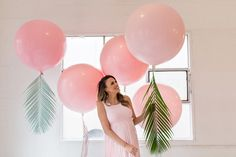 Pink balloons and tropical leaves