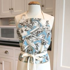 Made in USA retro apron with record players and vinyl albums. Make your favorite cocktail and put your favorite vinyl album on the hi-fi, weather it's Patsy Cline, Crosby Stills and Nash, or the Beatles this apron will have you dancing while dishing the dinner. Vintage turntables on a blue background make this made in USA apron a retro golden oldie. Waist ties are long and can be tied in the front or back. Adjustable neck strap. The apron features contrasting double topstitching. Makes a…