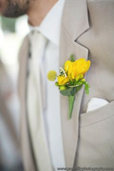 Groom's Boutonniere of bright yellow freesia, billy balls and green hypericum berry accents
