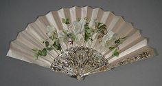 A late 19th Century mother of pearl fan, the pierced sticks decorated in gilt and silver, the silk panel painted with full blown roses, 12.75ins, with box for same
