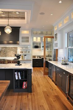 I like how this works - kitchen is white above with white countertops.  Yet the black cabinets and rustic wood floor add contrast and the kitchen is still classic. (black and white will never go out of style).