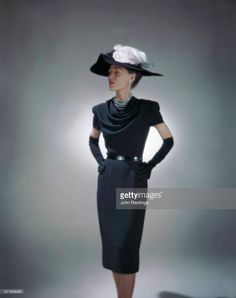 Model wearing black rayon dinner dress with cap sleeves and draped neckline by Omar Kiam for Ben Reig.