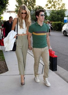 delta goodrem in highwaisted pants and a little crop top and arm candy in the form of nick jonas.