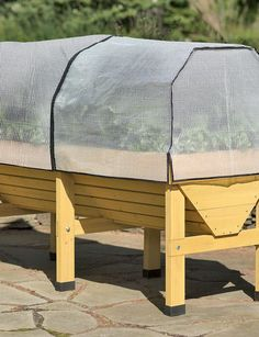 raised patio planter with covers. I bet we could DIY something like this. It would sure make gardening a lot easier for me if it was easy to reach. Would be gorgeous on the deck!