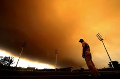 Jogador de críquete observa céu encoberto por fumaça alaranjada em campo de treinamento na cidade de Sydney, na Austrália - http://epoca.globo.com/tempo/fotos/2013/10/fotos-do-dia-17-de-outubro-de-2013.html (Foto: Mark Metcalfe/Getty Images)