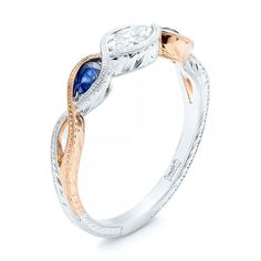 This elegant engagement ring features a Marquise diamond bezel set in the center, with pear shape blue sapphires bezel set on either side, and custom hand engraving on the two-tone shank. Designed and created by Joseph Jewelry | Seattle, WA | Bellevue, WA | Online | Design Your Own Engagement Ring | #engagementring