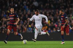 Jese of Real Madrid CF runs with the ball under pressure from Sergio Busquets and Daniel Alves of FC Barcelona during the La Liga match between FC Barcelona and Real Madrid CF at Camp Nou on April 2, 2016 in Barcelona