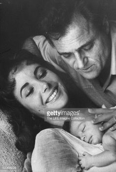 Producer Mike Todd gently embracing his wife actress Elizabeth Taylor and their baby daughter Liza